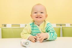 Petit bébé heureux s'asseyant à la table et aux sourires Image stock