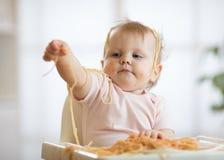 Petit bébé mangeant son déjeuner et faisant un désordre photos stock