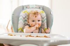 Petit bébé mangeant son dîner et faisant un désordre images libres de droits