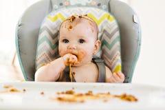 Petit bébé mangeant son dîner et faisant un désordre photo stock