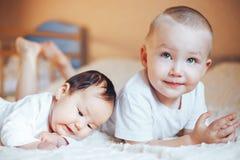 Petit bébé mignon avec le frère aîné se trouvant sur le lit à la maison photographie stock libre de droits