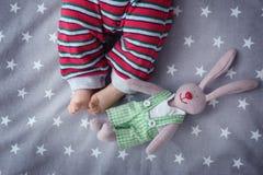 Petit bébé mignon avec le jouet de lapin se situant dans le berceau photo libre de droits