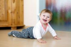 Petit bébé mignon heureux de sourire apprenant à ramper Image libre de droits