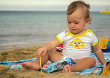 Petit bébé mignon jouant avec le sable près de la mer au coucher du soleil, Photos stock