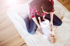 Petit bébé obtenant habillé par sa mère Photographie stock
