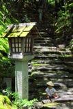 Petit bébé portant qu'une coutume de yukata des jeux traditionnels avec la forêt laisse tout en se reposant au-dessus des étapes  Photographie stock libre de droits