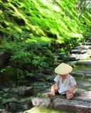 Petit bébé portant qu'une coutume de yukata des jeux traditionnels avec la forêt laisse tout en se reposant au-dessus des étapes  Image stock