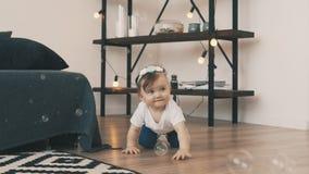 Petit bébé rampant sur le plancher dans la chambre avec la jeune mère banque de vidéos