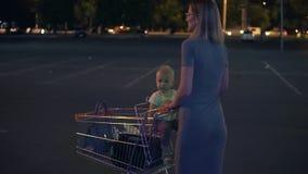 Petit bébé s'asseyant dans un chariot d'épicerie, alors que sa mère pousse le chariot marchant en avant au parking par clips vidéos