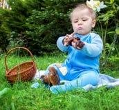 Petit bébé s'asseyant sur l'herbe en parc et semblant étudié sur le champignon Images libres de droits