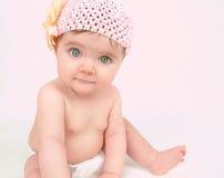 Petit bébé s'asseyant sur le rose Images stock