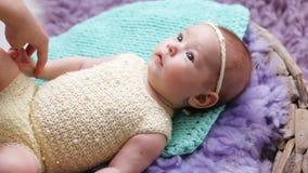 Petit bébé se trouvant sur un berceau de lit avec le pourpre et la turquoise banque de vidéos