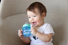 Petit bébé souriant heureusement et tenant la bouteille avec de l'eau dans des ses mains photos libres de droits