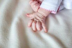 Petit bébé tenant la main du ` s de mère Images stock