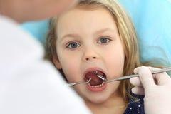 Petit b?b? s'asseyant ? la chaise dentaire avec la bouche ouverte et crainte se sentante pendant le contr?le oral vers le haut du photo stock
