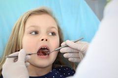 Petit b?b? s'asseyant ? la chaise dentaire avec la bouche ouverte pendant le contr?le oral vers le haut de tandis que docteur Bur image libre de droits