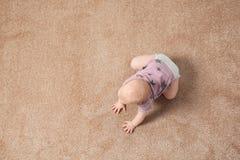 Petit b?b? mignon rampant sur le tapis ? l'int?rieur photos stock