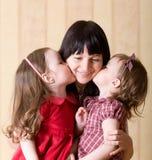 Petit baiser du descendant deux leur mère Images stock