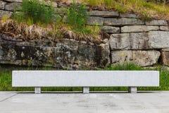 Petit banc de mur en béton par la falaise de roche Photo libre de droits