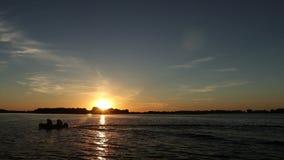 Petit bateau au coucher du soleil sur la rivière banque de vidéos