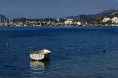 Petit bateau avec la marina et les montagnes derrière Photographie stock libre de droits