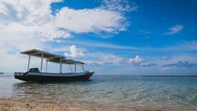 Petit bateau avec un toit se tenant à côté d'une plage sablonneuse dans l'océan ouvert, où il y a de petites vagues clips vidéos