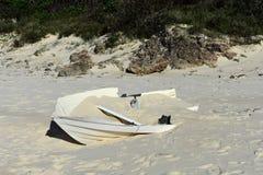 Petit bateau détruit sur une plage photos stock