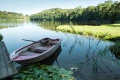Petit bateau dans le lac en montagne avec le champ vert et le ciel bleu Image libre de droits