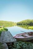 Petit bateau dans le lac en montagne avec le champ vert et le ciel bleu Photo libre de droits