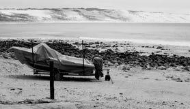 Petit bateau de pêche couvert sur la plage tranquille (noire et blanche) Photographie stock libre de droits