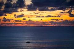 Petit bateau de pêche en bois au coucher du soleil dans l'océan Photos stock