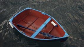 Petit bateau de pêche en bois avec un aviron bleu simple à l'intérieur, attaché près d'un pilier contre l'eau foncée et sombre d' photo libre de droits