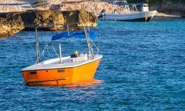 Petit bateau de pêche orange lumineux, bateau de touristes à une île tropicale Image libre de droits