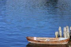 Petit bateau en bois amarré à de vieux empilages images stock