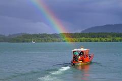 Petit bateau rouge sur le fleuve avec l'arc-en-ciel Photo libre de droits