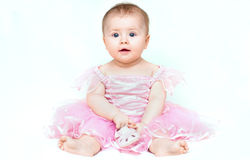 Petit bébé adorable dans la robe rose jouant avec sa chaussure rose Photographie stock