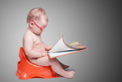 Petit bébé avec des verres se reposant sur la toilette Photographie stock libre de droits
