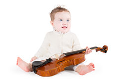 Petit bébé drôle jouant avec un grand violon Image libre de droits