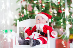 Petit bébé garçon nouveau-né dans le costume de Santa sous l'arbre de Noël Image stock