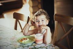 Petit beau garçon de sourire mignon s'asseyant à la table Tarte de plat vert et d'un verre de lait devant lui L'impression d'a photo stock