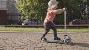 Petit beau garçon sur le scooter de coup-de-pied en parc Mouvement lent clips vidéos