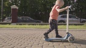 Petit beau garçon sur le scooter de coup-de-pied en parc Mouvement lent banque de vidéos