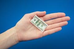 Petit billet d'un dollar américain à disposition sur un fond bleu Photos stock