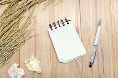 Petit bloc-notes de papier de carnet pour écrire l'information avec le stylo et les boules de papier chiffonnées sur la table en  Image stock