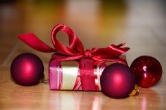 Petit boîte-cadeau avec le ruban rouge sur un fond en bois Image libre de droits