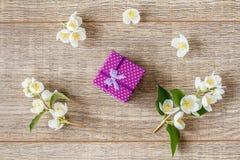 Petit boîte-cadeau enveloppé avec le ruban violet sur le décor de conseils en bois Images libres de droits