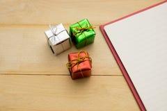 Petit boîte-cadeau trois mettant à côté de la page de carnet sur le CCB en bois Image libre de droits