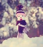 Petit bonhomme de neige dans la neige avec un chapeau et une écharpe tricotés photographie stock libre de droits