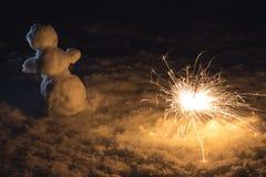 Petit bonhomme de neige dans la neige tenant le cierge magique proche Image stock