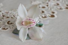 Petit bouquet de boutonniere blanc d'orchidée pour la boutonnière utilisée pour des invités de marié et de mariage placés sur un  Photos stock